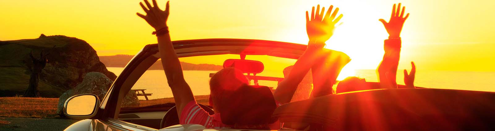 Couple raising their hands up in a convertible